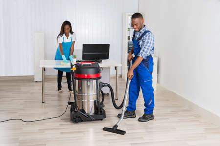 Young Male And Female Janitor Cleaning Office With Vacuum Cleaner