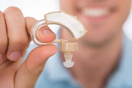 Primer plano de audífono mano que sostiene el hombre