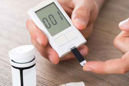 blood glucose level: Close-up Of Patient Hands Measuring Glucose Level Blood Test With Glucometer