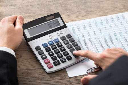 registros contables: Close-up Of A Businessman Analyzing Accounting Document With Calculator At Desk In Office