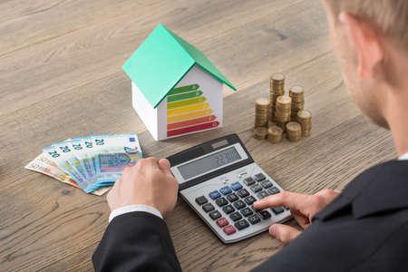 Geschäftsmann Unter Verwendung des Rechners in der Nähe von Haus Modell aus Energieeffizienz mit Münzen auf Schreibtisch