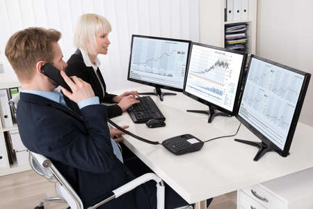 businesspeople: Two Businesspeople Analyzing Stock Charts On Multiple Computer Screens