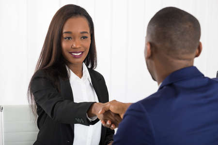 black hands: Two Successful African American Businesspeople Shaking Hands At Office