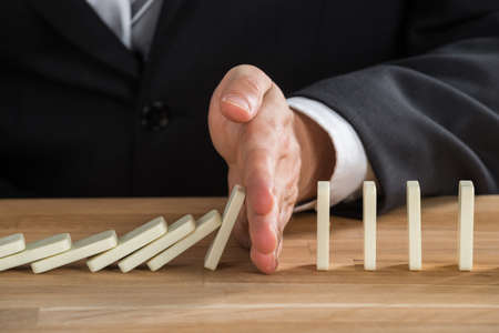 dominoes: Close-up Of Young Businessperson Stopping Dominos From Falling On Wooden Desk