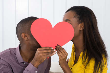 Close-up Of Young African Couple Hiding Behind Heart Shape