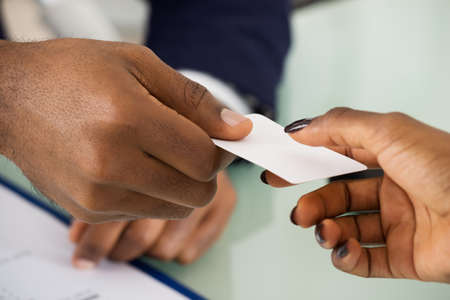 identity card: Close-up Photo Of Businesspeople Exchanging Name Card