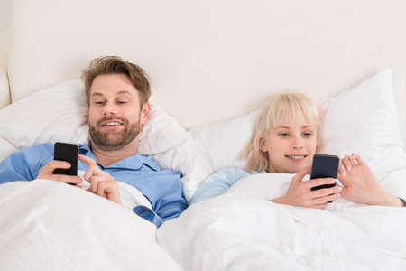 bedcover: Young Happy Couple Using Cellphones While Lying On Bed At Home