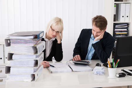 invoices: Two Young Businesspeople Calculating Invoices In Office
