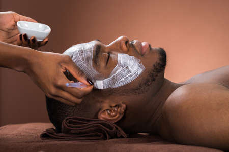 black guy: Therapist Applying Face Mask To Young African Man In Spa