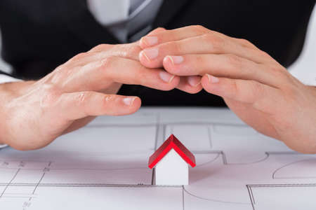 male hand: Close-up Of Young Male Architect Hand Sheltering House Model On Blueprint In Office