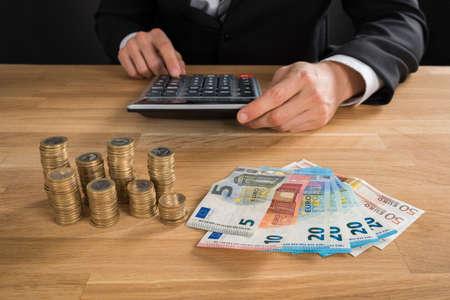 incremento: Primer plano del hombre de negocios joven que usa la calculadora con las monedas y billetes de banco en Escritorio Foto de archivo