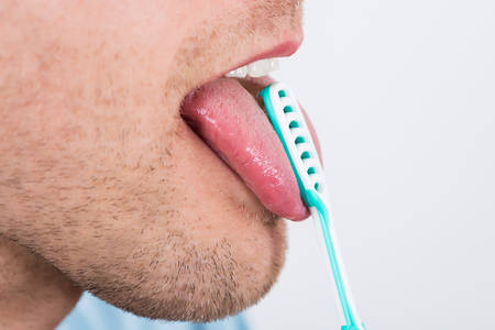 scraper: Close-up Of Young Man Cleaning His Tongue With Scraper