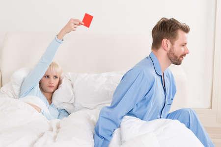 ベッドで男にレッド ・ カードを示す不幸な若い女性 写真素材