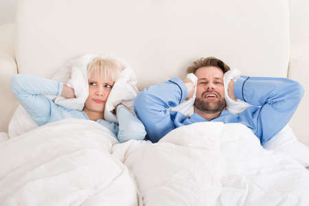 annoying: Young Unhappy Couple Covering Ears While Sleeping On Bed At Home