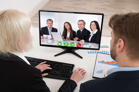 Two Young Businesspeople Video Conferencing On Computer At Office photo