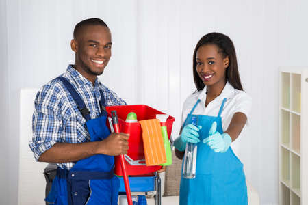 Portrait Of Happy African Male And Female Janitors