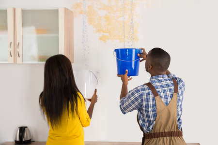 drop ceiling: Young African Woman Standing With Worker Collecting Water In Bucket From Ceiling In House