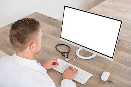usando computadora: Joven doctor de sexo masculino que usa el ordenador en el escritorio en la Clínica Foto de archivo