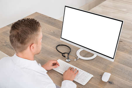 using computer: Young Male Doctor Using Computer On Desk In Clinic Stock Photo