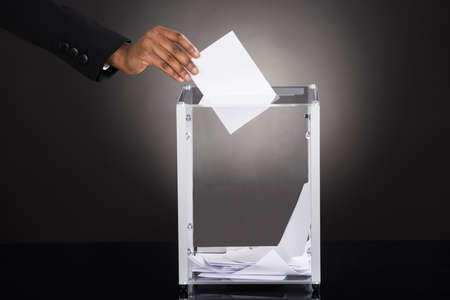 inserting: Close-up Of A Businessperson Hand Inserting Ballot In Glass Box Against Gray Background