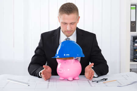 rounder: Young Male Architect With Piggybank Wearing Construction Helmet On Blueprint At Desk In Office