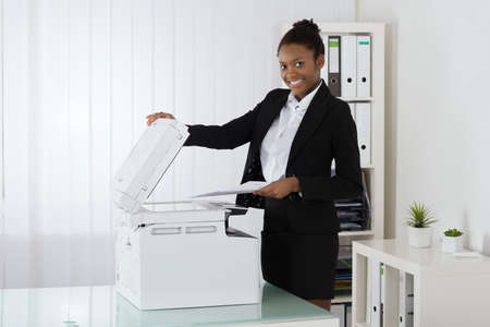 photocopy: Smiling Young African Businesswoman Placing Paper On Photocopy Machine In Office