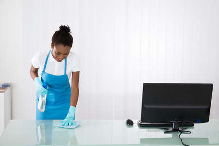 janitor: Happy Young African Female Janitor Cleaning Desk With Rag In Office