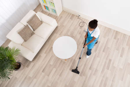 High Angle View Of Young African Female Janitor Cleaning Hardwood Floor With Vacuum Cleaner