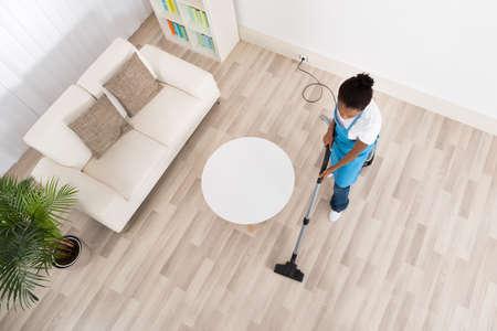 Vue en plongée De Jeune Femme africaine Janitor Nettoyage Sol en bois Avec Aspirateur