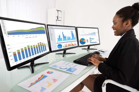 Jonge Afrikaanse Zakenvrouw analyseren van grafiek op meerdere computer op kantoor Stockfoto