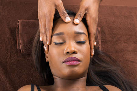 Relaxed Young African Woman Receiving Forehead Massage In Spa