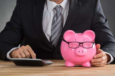 smart investing: Close-up Of Businessman Using Calculator To Calculate With Piggybank On Desk