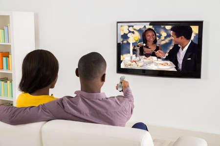 Pareja africana felices viendo la televisión en casa