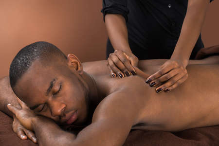 pressure massage: Young African Man Getting Massage In Spa