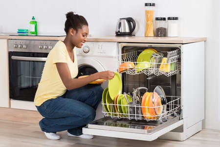 arranging: Happy Young Woman Arranging Plates In Dishwasher At Home