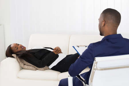 black professional: African American Woman Laying On Couch In Front Of Psychiatrist With Clipboard Stock Photo