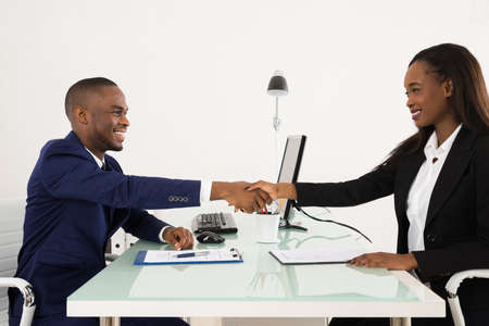 Apretón de manos acertado de negocios estadounidense con el cliente en la oficina Foto de archivo