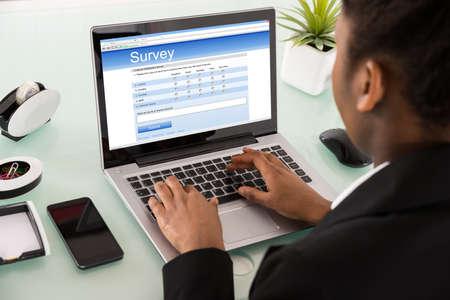Close-up von einem jungen afrikanischen Geschäftsfrau Filling Online-Umfrage Formular auf Laptop