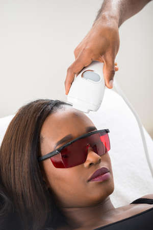 Close-up Of Therapist Giving Laser Epilation Treatment To Young African Woman