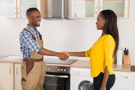 serviceman: Young Serviceman And Woman Handshaking In Kitchen