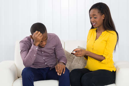 stress testing: Sad Expectant Couple Holding Pregnancy Test Sitting On Sofa At Home Stock Photo