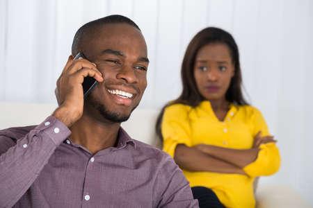 Mujer joven que mira al hombre que habla en el teléfono celular en el país Foto de archivo