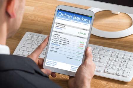Primer Del Empresario Joven de banca en línea que usa la tablilla digital en el ordenador de escritorio