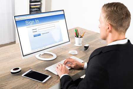 account executive: Young Businessman Signing Into A Website On Computer At Office Stock Photo