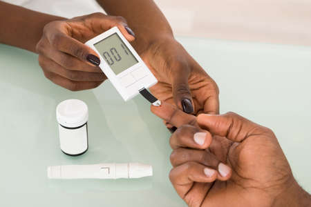 blood sugar: Close-up Of Hands Using Lancet On Finger Testing For Diabetes Stock Photo