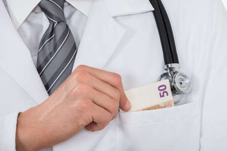 doctor money: Close-up Of Male Doctor Hand Putting Money In Pocket