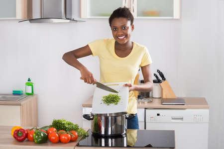 Feliz joven africana Poner las verduras picadas En utensilio Foto de archivo - 56064716