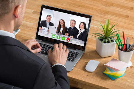 Close-up Of Young Businessman Video Conferencing On Laptop At Desk In Office photo