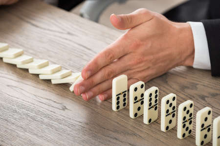finance problems: Close-up Of A Businessman Hand Stopping Dominoes From Falling On A Desk In Office