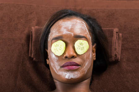 exfoliate: Close-up Of African Woman With Facial Mask In Spa Stock Photo